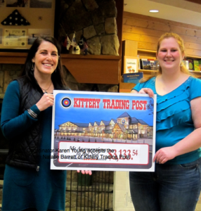 MtA2C Coordinator Karen Young accepts the donation from Natalie Barrett of Kittery Trading Post